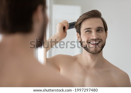 Happy handsome young shirtless man combing smooth straight hair, looking in mirror, enjoying beauty care activity, satisfied with haircare cosmetic products, haircut, barber work result Foto stock ©