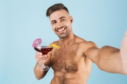 Happy handsome young shirtless man wearing beach shorts standing isolated over blue background, taking a selfie while drinking cocktail