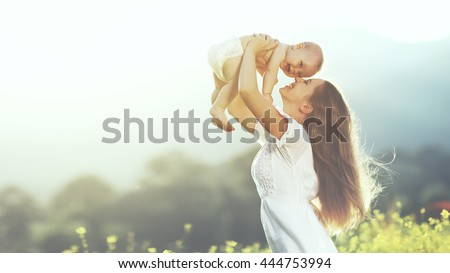 happy harmonious family outdoors. mother throws baby up, laughing and playing in the summer on the nature