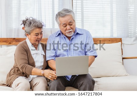 Happy healthy Asian senior elderly couple web chat on computer at home. Retired man and woman enjoy shopping or streaming online via website by using laptop. Elder retirement activity and lifestyle