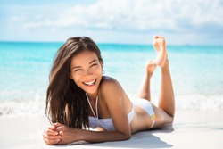 Happy healthy beautiful Asian multiracial woman lying down on sand enjoying sun tanning sunbathing in swimsuit relaxing on Caribbean tropical beach summer vacation. Smiling laughing girl.