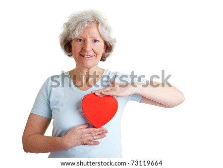 Happy healthy elderly woman holding a red heart