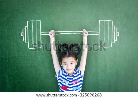 Happy healthy female kid doing weight lifting on grunge green chalkboard background: International day of girl child, equality and opportunity awareness on woman human rights, children\'s day concept