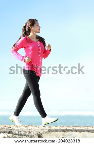 Happy healthy girl doing a brisk walking on the beach