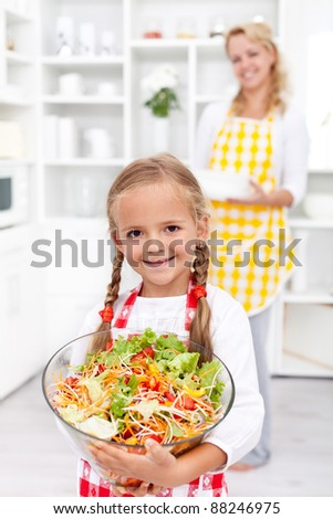 Happy healthy girl with large bowl of fresh vegetables salad in the kitchen