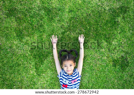 Happy healthy kid lying on green grass field raising two hands up with world map in the background : Little Asian child open arms with happiness in clean environment : Children in environment concept