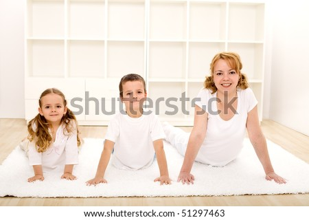 Happy healthy kids and their mother doing gymnastic exercises - healthy life concept
