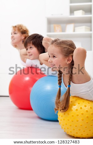 Happy healthy kids exercising together with their mother