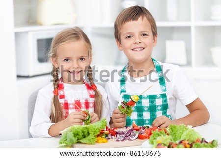 Happy healthy kids preparing a vegetables meal in the kitchen
