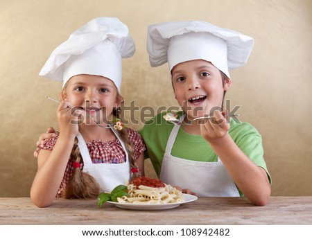 Happy healthy kids with chef hats eating fresh pasta - italian cuisine concept