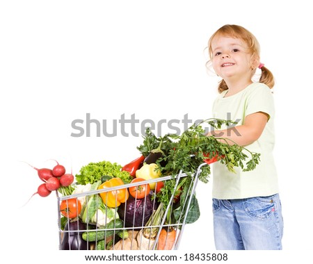 Happy healthy little girl with vegetables in shopping cart - isolated