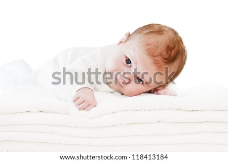 Happy healthy newborn baby boy with blue eyes is lying crawling on a pile of towels and looking at us. Studio isolated on white background. Closeup. Look at my other baby shots in different situations