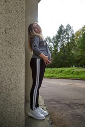 Happy healthy pregnancy and maternity. Portrait of pregnant young Caucasian woman wearing long blue dress posing near brick wall building outside. Beautiful hipster girl with big belly