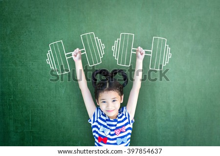 Happy healthy strong super powerful kid weight lifting exercise on grunge green chalkboard background: World health day WHD: Gender parity on human rights  Children\'s day concept Women\'s leader idea
