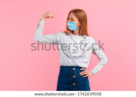 Happy healthy strong young woman in a medical protective mask on her face, showing biceps on her arm, on an pink background