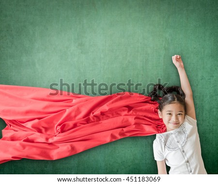 Happy healthy superhero strong powerful little Asian school student girl kid with red scarf dress costume in flying pose on grunge green chalkboard background: Girl power super woman education concept