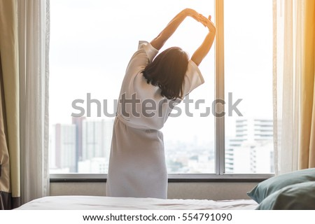 Happy healthy woman's back view waking up stretching in bed room hotel/ home interior at glass wall window, city background: Simple lifestyle people get up in cozy indoor comfortable relaxing space #554791090