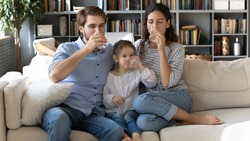 Happy healthy young family drinking pure mineral water together, thirsty dehydrated mother and father with cute little daughter holding glasses, sitting on couch in living room, healthy lifestyle