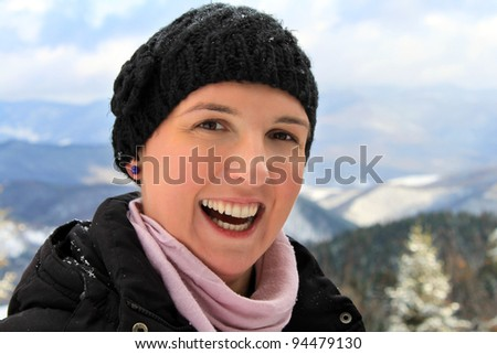 Happy healthy young woman with a big smile on her face, having fun, on a mountain covered with snow, happiness concept