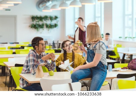 happy high school students taking lunch together at school cafeteria