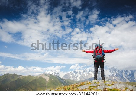 Happy hiker winning reaching life goal, success man at summit. Young hiker holding arms outstretched, freedom and happiness, achievement in mountains