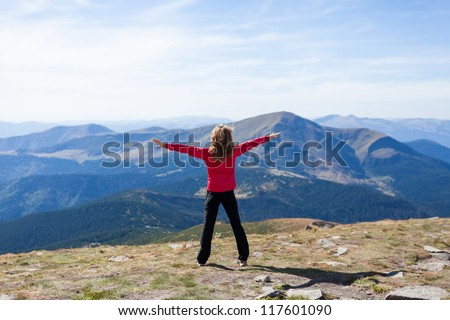 Happy hiker woman standing on a peak over the mountain with raised hands embracing vitality freedom feeling success and looking to a sky. Position back to us