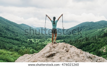 Happy hiker young woman with trekking poles standing on peak of cliff in summer mountains #476021260