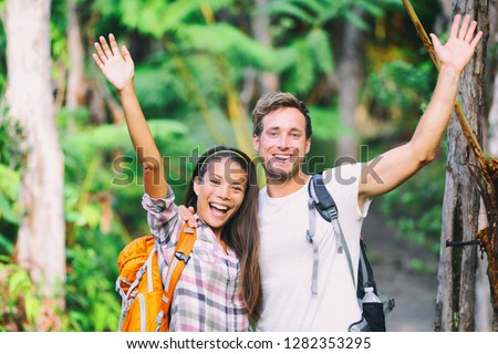 Happy hiking - hikers cheering joyful in forest. Cheerful excited hiker couple with arms raised up outstretched in joy smiling happy looking at camera. Multiethnic man and woman on outdoor hike.