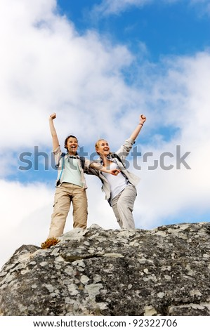 happy hiking women have made it to the summit and they raise their arms up in joy