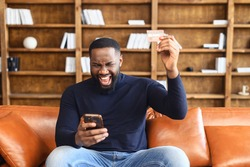 Happy hilarious young multiracial man involved in online shopping, celebrating getting gift or winning prize in giveaway, paying for goods or services with credit bank card in smartphone application
