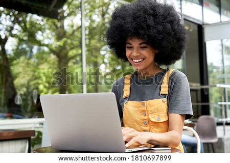 Happy hipster African American female student, freelancer with Afro hair using laptop computer sitting at table in outdoor cafe elearning, remote studying, typing on pc tech, working on internet.