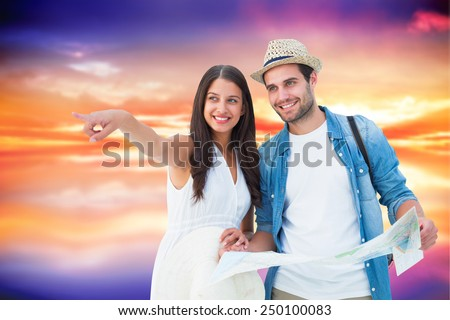 Happy hipster couple looking at map against purple sky with orange clouds