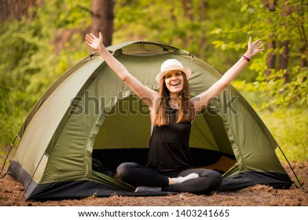 Happy hipster cute teen girl with hands enjoying sunrise outside the tent. camping in forest. Enjoy nature freedom #1403241665