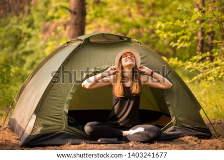 Happy hipster cute teen girl with hands enjoying sunrise outside the tent. camping in forest. Enjoy nature freedom #1403241677
