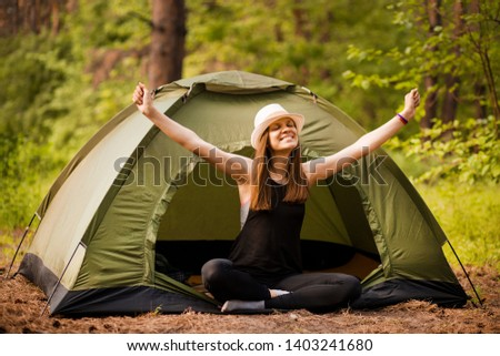 Happy hipster cute teen girl with hands enjoying sunrise outside the tent. camping in forest. Enjoy nature freedom #1403241680