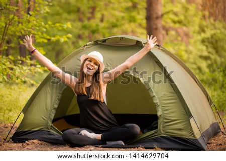 Happy hipster cute teen girl with hands enjoying sunrise outside the tent. camping in forest. Enjoy nature freedom #1414629704