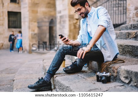 Happy hipster guy laughing at funny video from social network browsed on cellular connected to 4G internet, positive male traveler blogging via smartphone enjoying connection in roaming outdoors