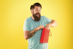 Happy hipster hold paper bag. Bearded man smiling with purchase. Impulse purchase. Shopping concept. Shop store mall boutique. Buy product. Aspects can influence customer decision making behavior.