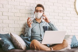 Happy hipster man freelancer in medical face mask talking mobile phone, sitting on couch with laptop on laps. Young businessman in protective mask working with computer at home office. Remote business