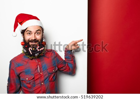 Happy hipster man in santa hat with funny christmas decorated beard pointing to the side at copy space over white and red background