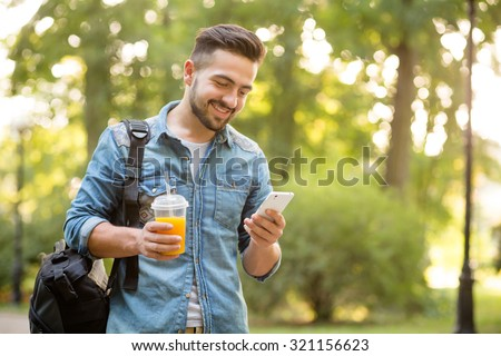 Happy hipster man walking in autumn park and smiling. Short-haited man looking at mobile phone\'s screen and enjoying reading messages.