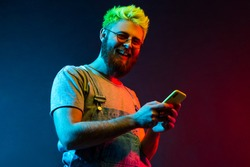 Happy hipster man with beard and green hair looking at camera with toothy smile and holding mobile phone in hands, being in good mood, has great news. Colorful neon light, indoor studio shot.