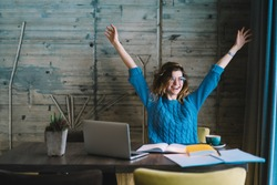 Happy hipster student rejoicing in success of training project holding hands up.Overjoyed young woman completed studying task during exam preparation sitting at desktop with laptop and textbook