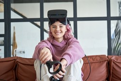 Happy hipster teen girl pink hair wear vr glasses headset hold controllers sit on sofa look at camera. Digital innovation video game, virtual reality 3D 360 video app education entertainment. Portrait