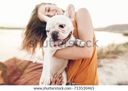 happy hipster woman playing with bulldog on the beach in sunset light, summer vacation. stylish girl with funny dog resting, hugging and having fun in sun, cute moments. space for text  #713530465