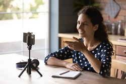Happy Hispanic blogger girl taking video on mobile phone with tripod, speaking at webcam. Employee, applicant using smartphone for remote call, job interview. Tutor, coach holding webinar from home.
