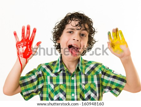 Happy Hispanic child gesturing at the camera with his two hands painted. Watercolor mess at home. Not a funny way to have fun. Kid enjoying his free time playing with watercolor paint.
