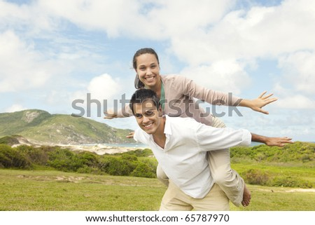 happy hispanic couple in love, man giving piggyback to woman