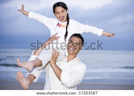 Happy Hispanic dad and 9 year old daughter having fun on beach