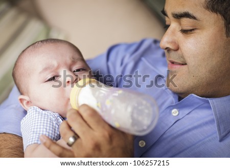 Happy Hispanic Father Bottle Feeding His Very Content Son.